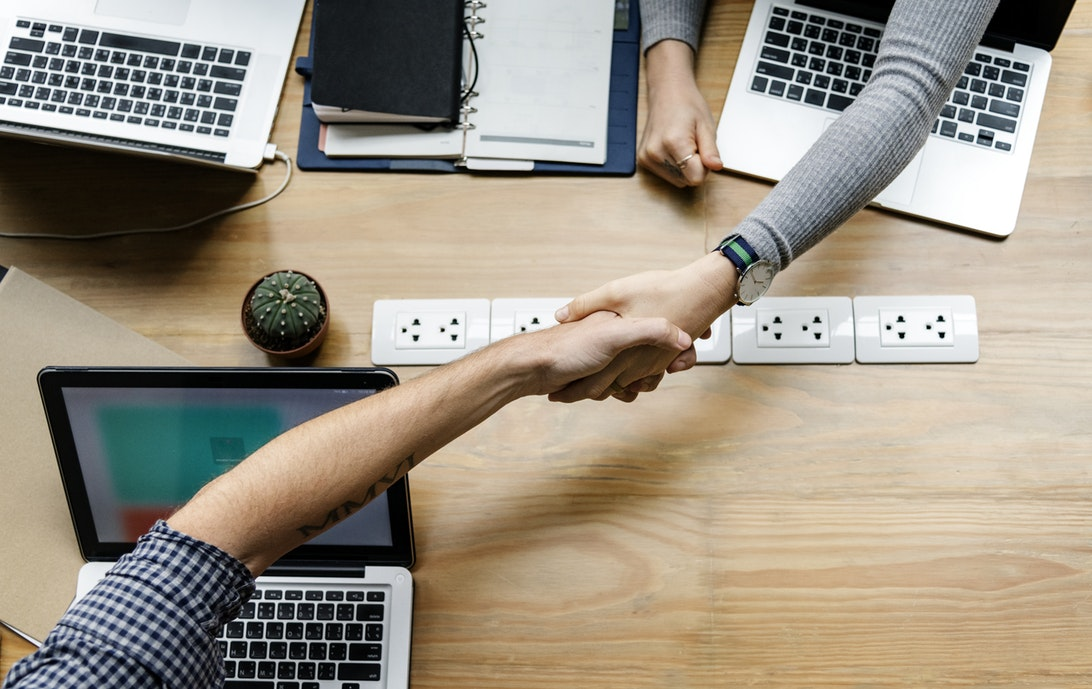 handshake over a table with laptops